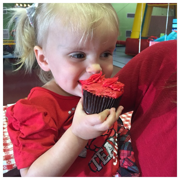 Two year old birthday party idea success with Elmo's World Birthday party theme idea. Smiling kid eating a red Elmo cupcake.